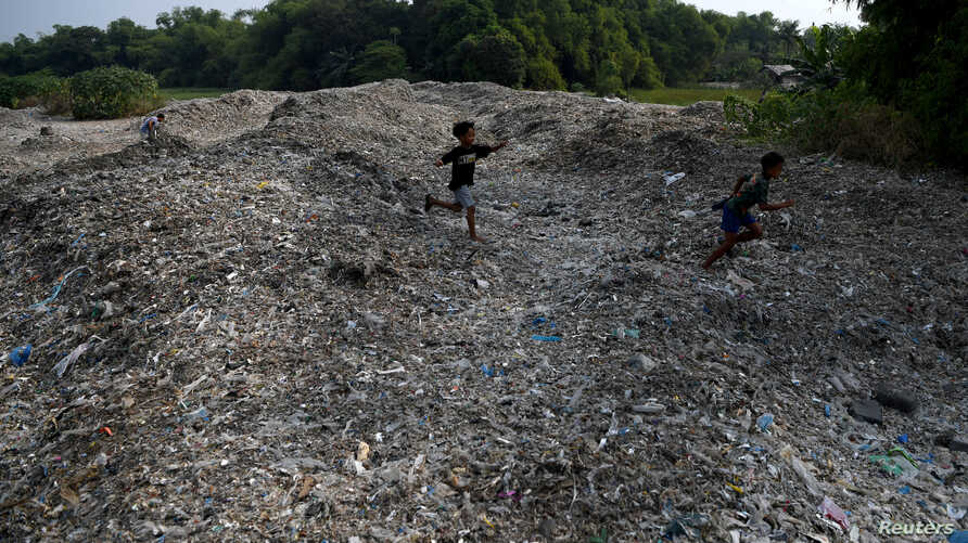 Kids play on piles of imported plastic waste in Mojokerto, East Java province, Indonesia, June 19, 2019.