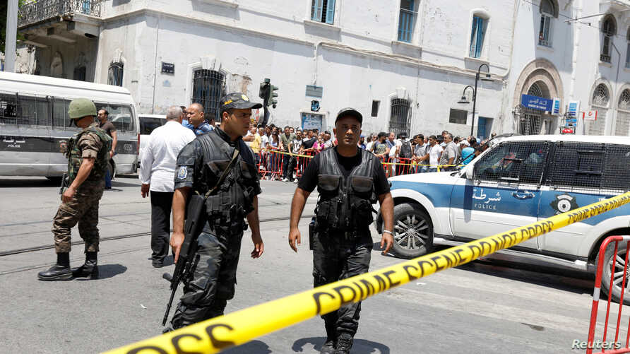 Police officers secure the site of a suicide bombing attack in downtown Tunis, Tunisia, June 27, 2019.