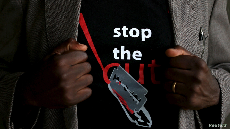 """FILE - A man shows the logo of a T-shirt that reads """"Stop the Cut"""" referring to Female Genital Mutilation (FGM) during a social event advocating against harmful practices such as FGM at the Imbirikani Girls High School in Imbirikani, Kenya, April 21, 2016."""