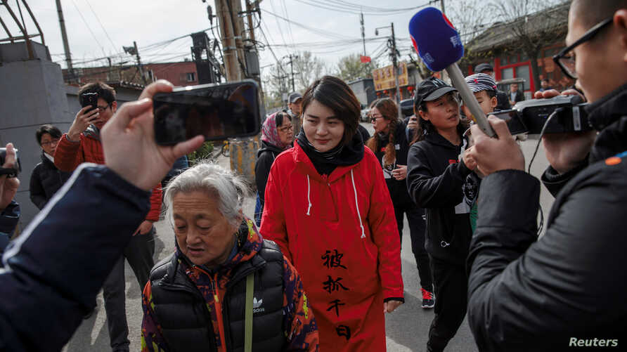 FILE - Li Wenzu, wife of detained Chinese rights lawyer Wang Quanzhang, is followed by friends and media near a Supreme People's Court complaints office in Beijing, China, April 4, 2018.