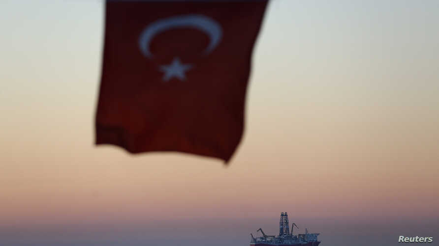 FILE - The Turkish national flag hangs in the foreground as drilling vessel Fatih is seen off the Mediterranean resort city of Antalya, Turkey