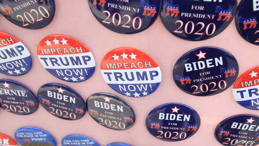 """FILE - Biden for President campaign buttons are for sale beside """"Impeach Trump Now!"""" buttons as U.S. Democratic presidential candidate and former Vice President Joe Biden meets union workers at the Teamsters Local 249 hall  in Pittsburgh, Pa., April 29, 2019."""