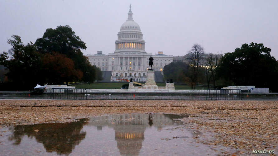 FILE - The U.S. Capitol building reflected in water at sunrise in Washington.