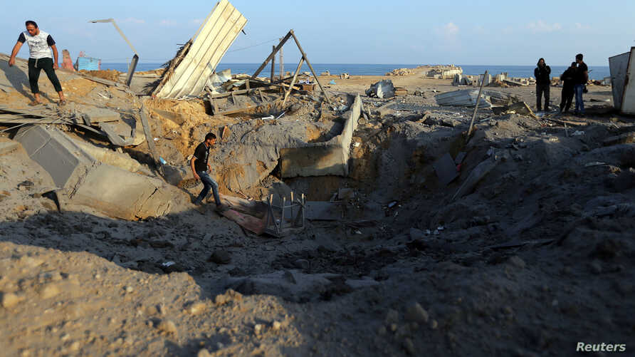 Palestinians inspect site of Israeli air strike in southern Gaza Strip, June 14, 2019.