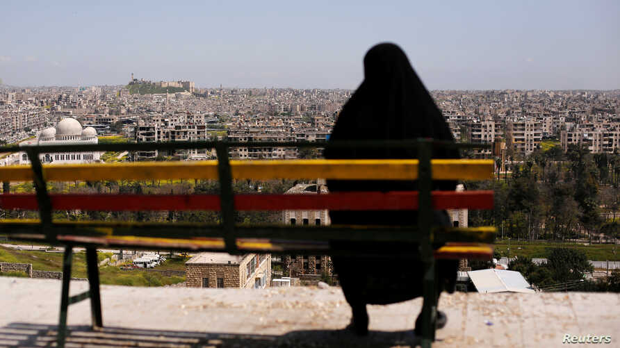 A woman sits on a bench overlooking Aleppo's ancient citadel and the old city, Syria April 13, 2019.