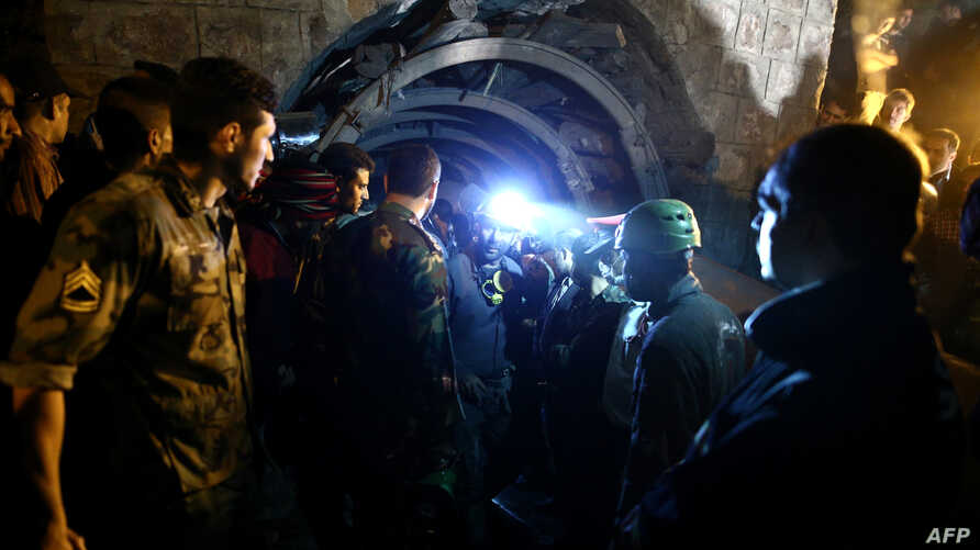 FILE - Coal miners and rescue workers are seen at a mine in Azadshahr, in northern Iran, following an accident.