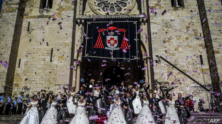 Brides and grooms pose for a photo outside Lisbon's Cathedral following their wedding ceremonies, in Lisbon, Portugal, June 12, 2019.