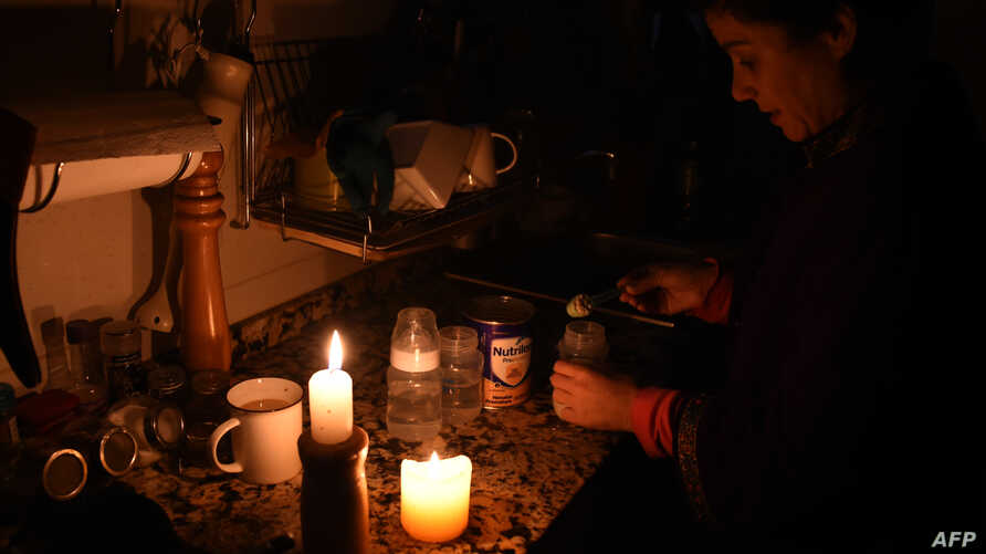 A woman prepares milk bottles using candles at her home in Montevideo, Uruguay, June 16, 2019, during a power cut.