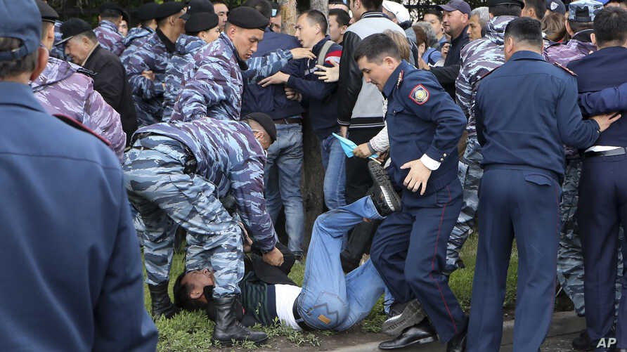 Police detain a demonstrator during an anti-government protest in Nur-Sultan, the capital city of Kazakhstan, June 9, 2019.