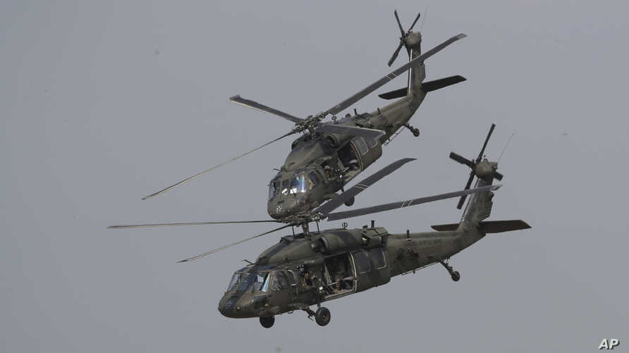 FILE - Two U.S. Black Hawk helicopters participate in a media demonstration.