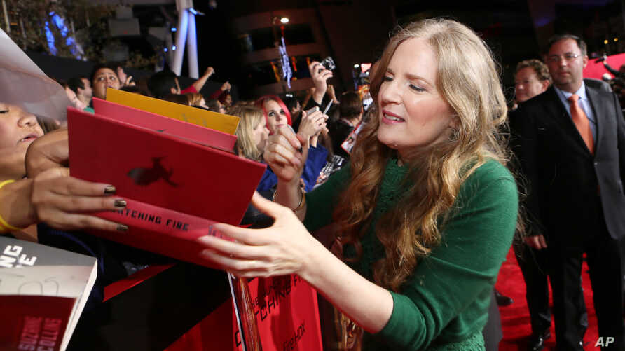 Author and executive producer Suzanne Collins signs a book at the premiere of Lionsgate's 'The Hunger Games: Catching Fire,' in Los Angeles, California, Nov, 18, 2013.