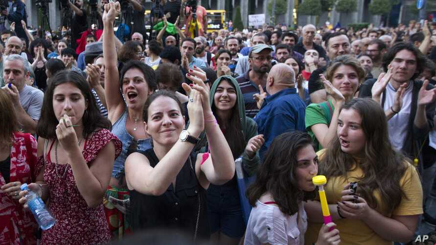 People applaud and listen to a speaker during a protest as opposition demonstrators gather in front of the Georgian Parliament building in Tbilisi, Georgia, June 24, 2019.
