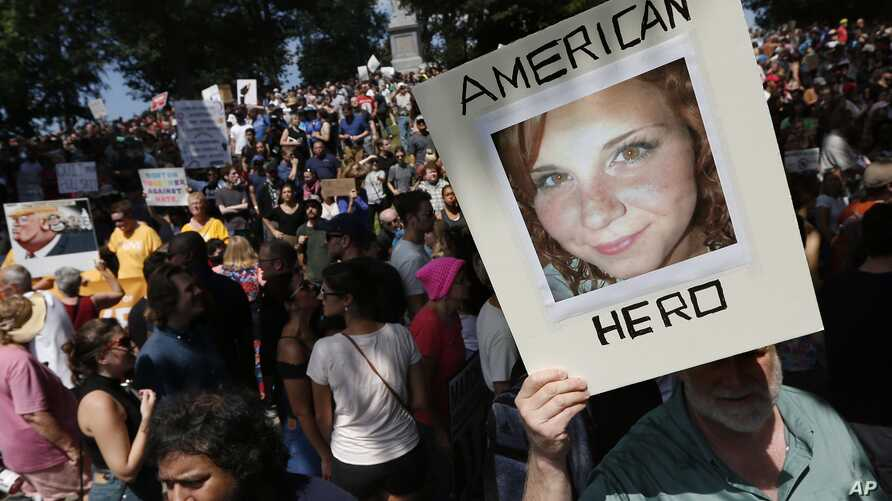 """FILE - A counter-protester holds a photo of Heather Heyer at a """"Free Speech"""" rally organized by conservative activists, in Boston, Massachusetts. Heyer was killed when a car, driven by James Alex Fields Jr., plowed into a group of people during protests in Charlottesville, Virginia."""