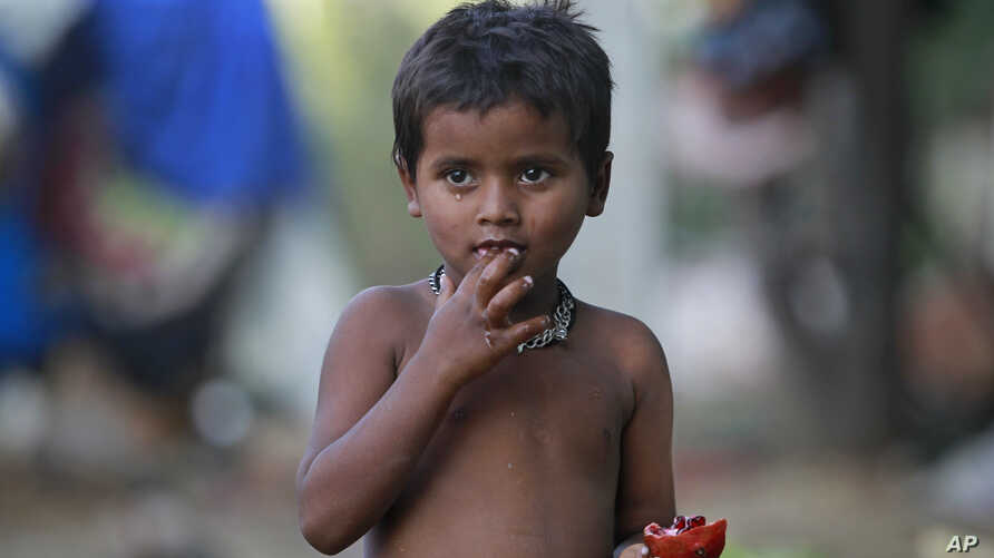A child eats a pomegranate collected from waste at a slum area on the outskirts of Jammu, India, Oct. 12, 2018.