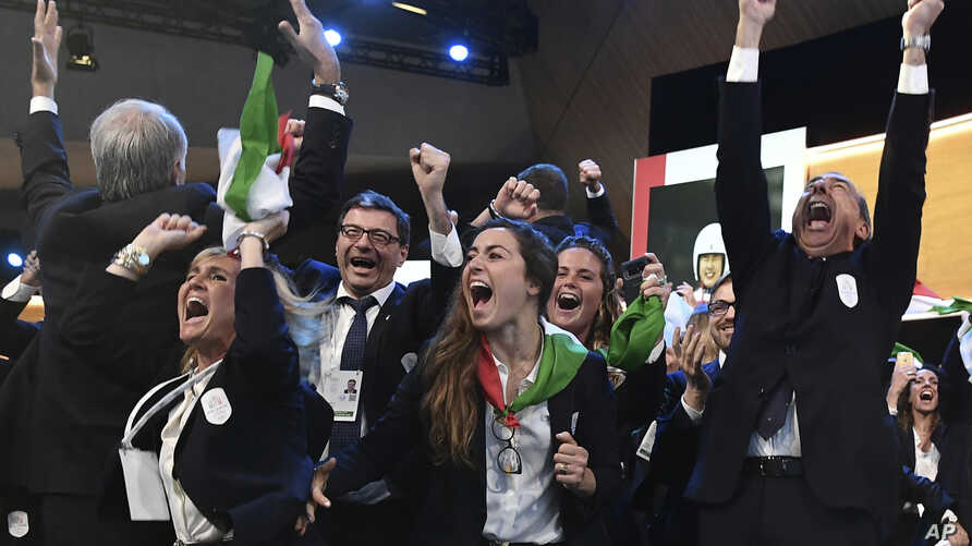 Mayor of Milan Giuseppe Sala, right, and members of the Milan-Cortina delegation celebrate after winning the bid to host the 2026 Winter Olympic Games, in Lausanne, Switzerland, June 24, 2019.