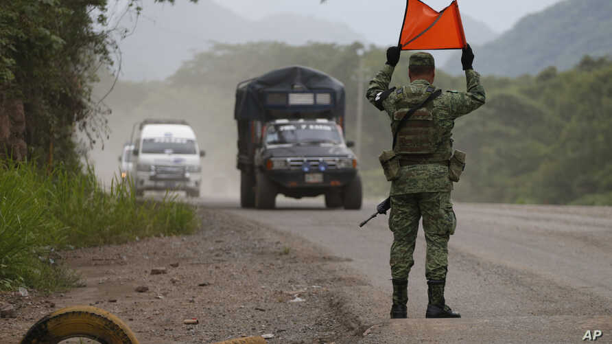 A soldier of Mexico's National Guard stops vehicles at a temporary checkpoint to look for migrants, just north of Ciudad Cuauhtemoc, Chiapas State, Mexico, June 15, 2019.