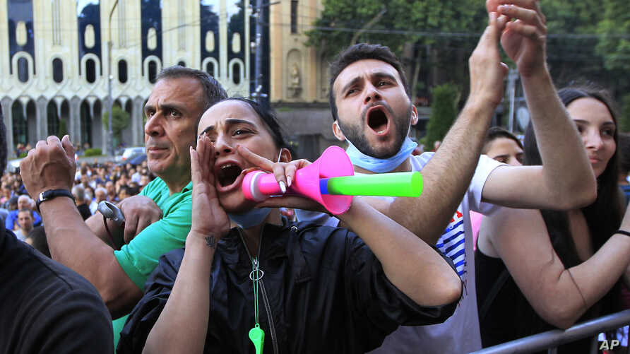 People react while listening to a speaker during a protest as opposition demonstrators gather in front of the Georgian parliament building, in Tbilisi, Georgia, June 24, 2019.