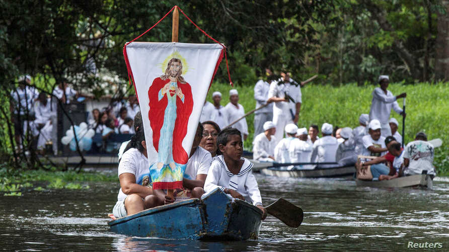 Roman Catholic pilgrims display a banner depicting Jesus Christ as they travel in a boat during an annual river procession along the Caraparu River in Santa Izabel do Para, in the Amazon jungle, Dec. 8, 2012.