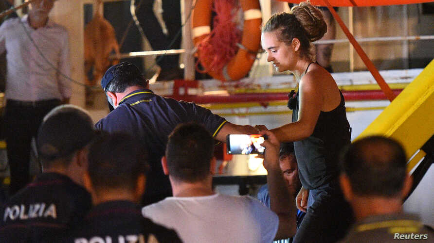 Carola Rackete, the 31-year-old Sea-Watch 3 captain, is escorted off the ship by police and taken away for questioning, in Lampedusa, Italy June 29, 2019.