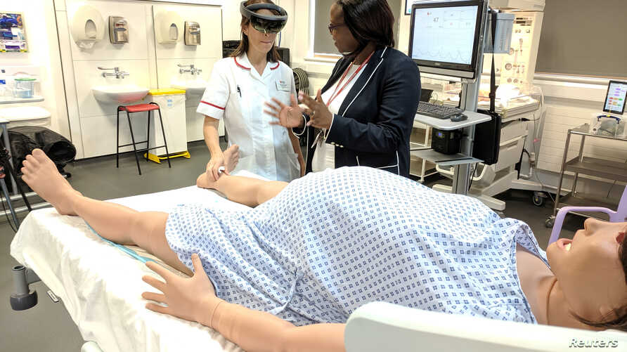 Midwifery educator at Middlesex University Sarah Chitongo instructs a trainee midwife wearing an augmented reality (AR) headset in London, Britain, June 17, 2019.