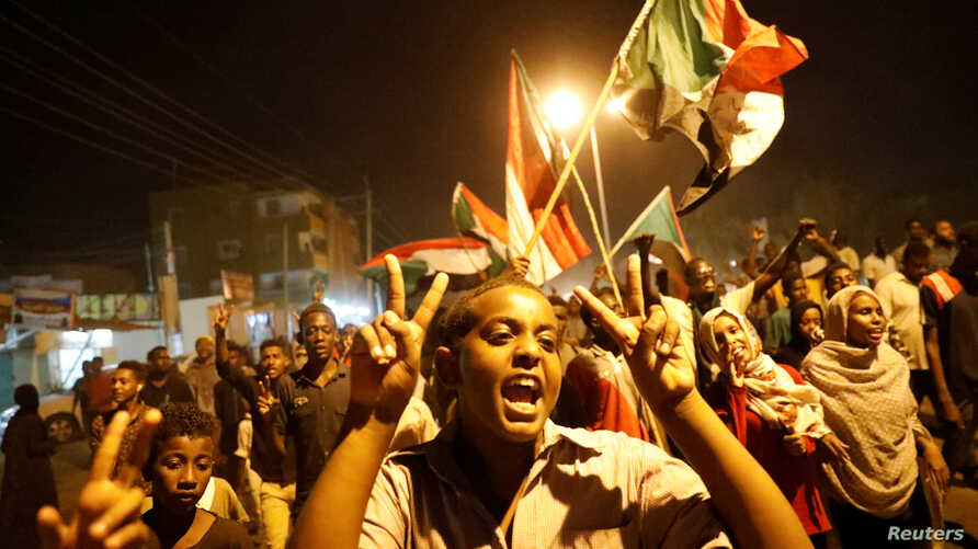 Protesters chant slogans and wave Sudanese flags during a rally in Khartoum, Sudan, June 21, 2019.