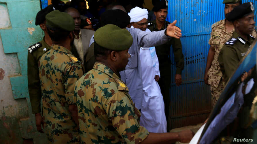 Sudan's former President Omar al-Bashir is escorted as he walks out from the National Prison in Khartoum, June 16, 2019