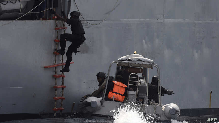 FILE - A Nigerian special guard climbs a ladder as he boards a vessel during a joint exercise between Nigerian and Moroccan naval personnel as part of a multinational maritime exercise off the coast of Lagos, March 20, 2019.