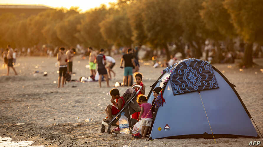 FILE - A Syrian family is seen in a tent on the beach at Menekse in Istanbul at sunset on July 28, 2019.