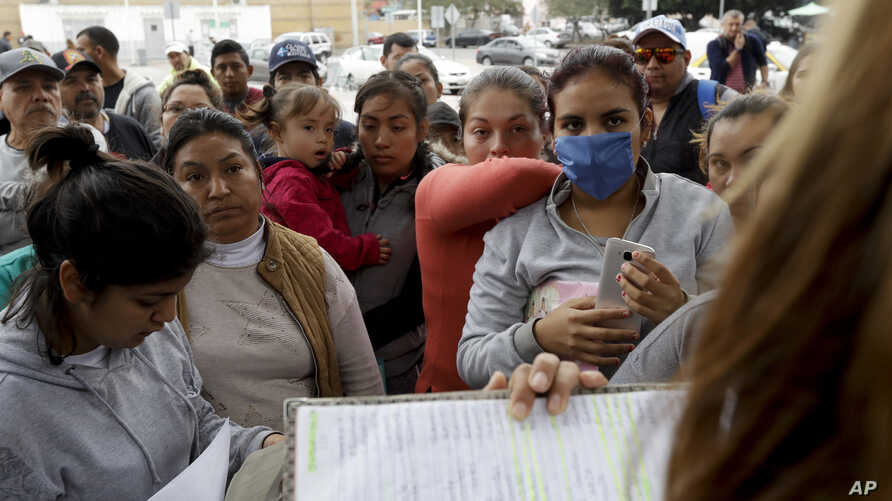 FILE - In this Oct. 23, 2018 file photo, women look on as numbers and names are called to cross the border and request asylum in the United States, in Tijuana, Mexico.