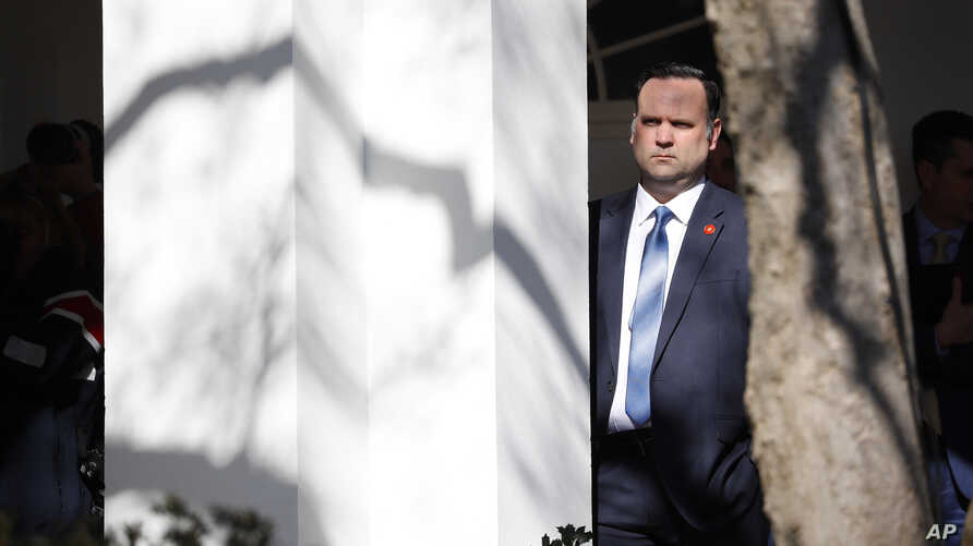 FILE - White House Social Media Director Dan Scavino listens to President Donald Trump speak during an event in the Rose Garden at the White House, Feb. 15, 2019.