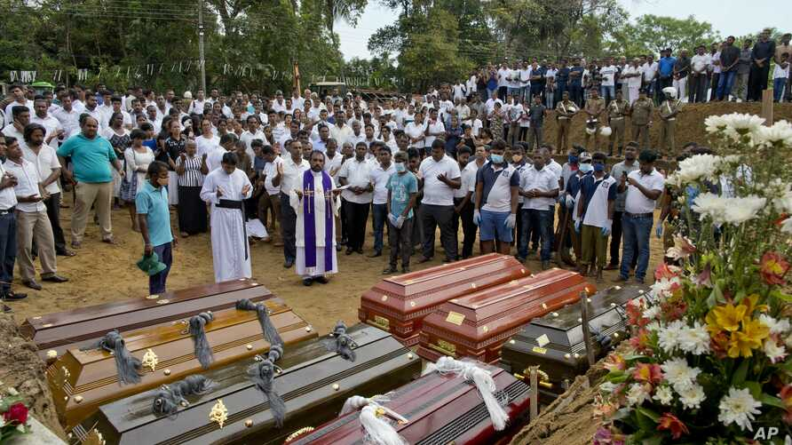 FILE - A priest conducts religious rituals during a mass burial for Easter Sunday bomb blast victims in Negombo, Sri Lanka, April 24, 2019.