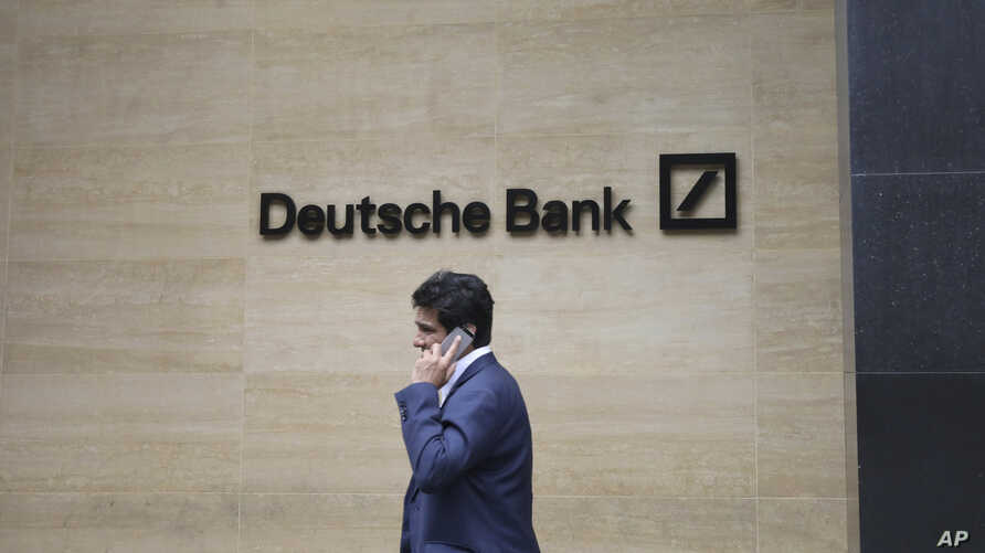 A man walks past the Deutsche Bank sign in London, July, 8, 2019.