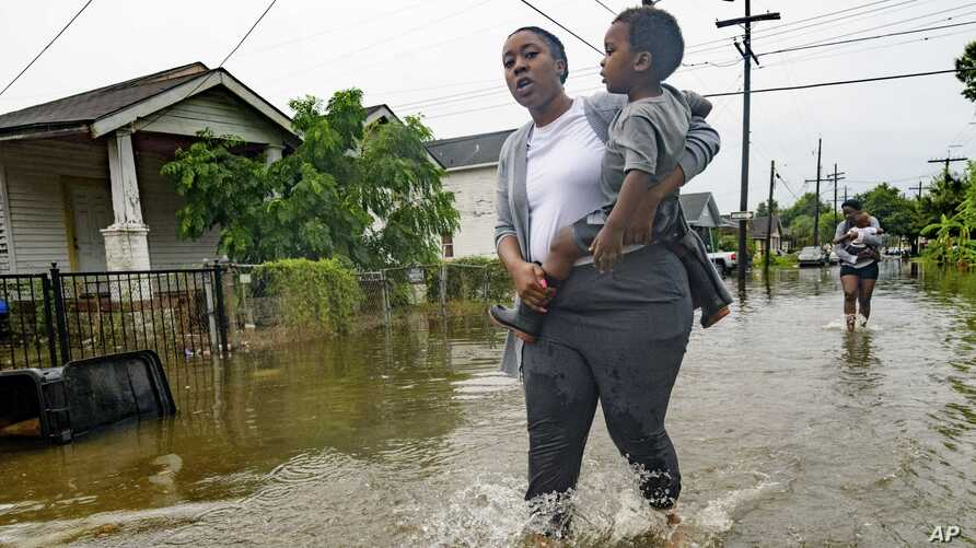 Terrian Jones reacts as she feels something moving in the water at her feet as she carries Drew and Chance Furlough to their mother on Belfast Street near Eagle Street in New Orleans after flooding from a 100-year storm from a tropical wave system in the Gulf Mexico dumped lots of rain in Wednesday, July 10, 2019.