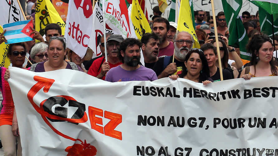 "People hold a banner reading ""No G7"" during a demonstration in Biarritz, southwestern France, July 13, 2019."