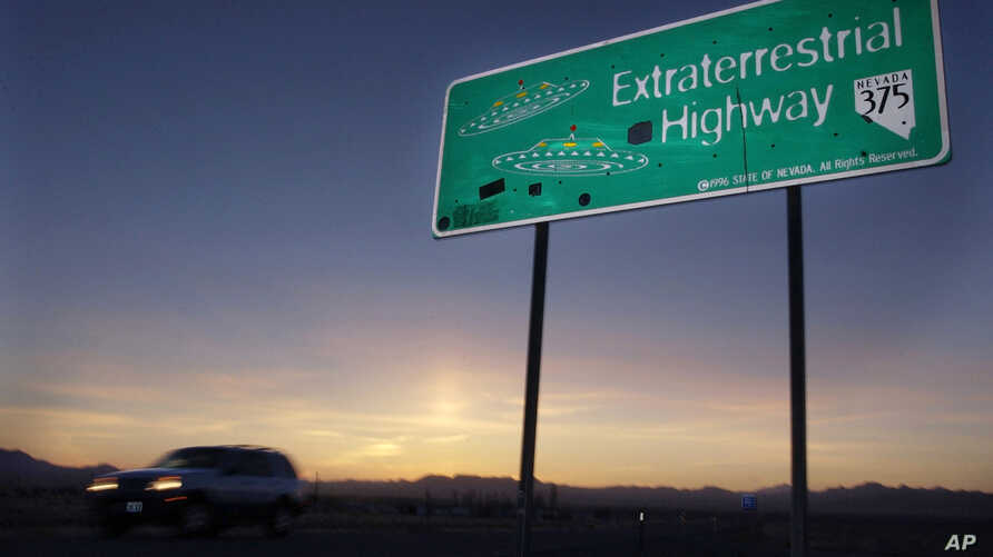 FILE - In this April 10, 2002, file photo, a car moves along the Extraterrestrial Highway near Rachel, Nev.