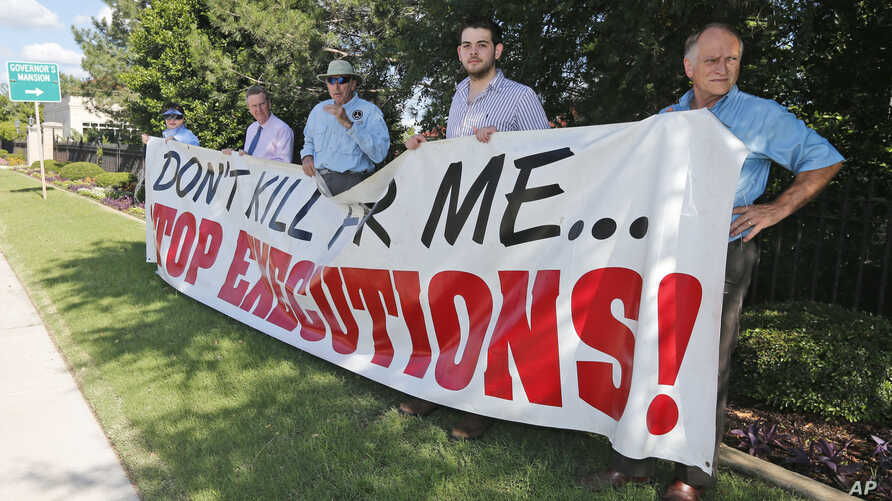 Protesters hold a sign against the death penalty outside the governor's mansion in Oklahoma City, June 18, 2013, protesting the execution of an inmate.