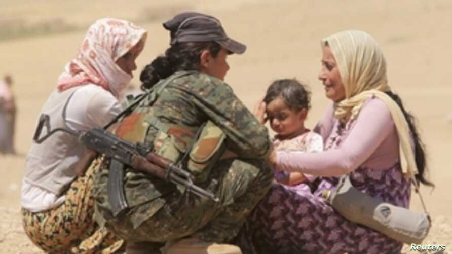 Displaced people from the minority Yazidi sect, fleeing violence from forces loyal to the Islamic State in Sinjar town, get help from a member of the YPG near the Syrian border.