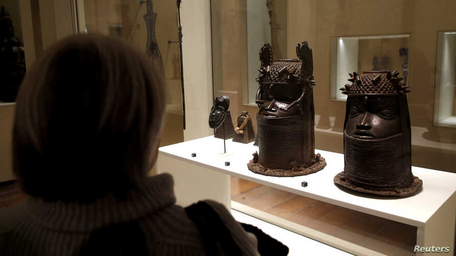FILE - A visitor looks at two heads of a royal ancestor from the former Benin Kingdom displayed at the Quai Branly Museum in Paris, France, Nov. 23, 2018.