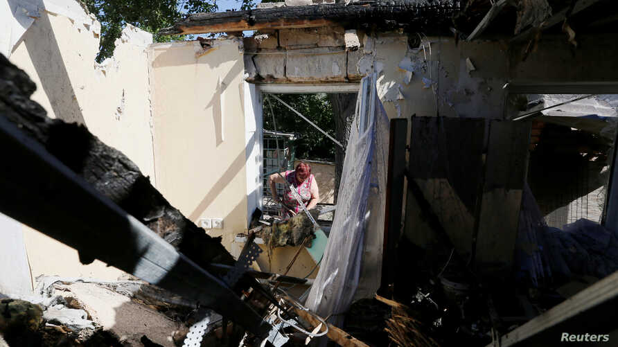 FILE - A local resident removes debris inside the house, which locals said was damaged during a recent shelling, in the rebel-controlled city of Donetsk, Ukraine June 17, 2019.