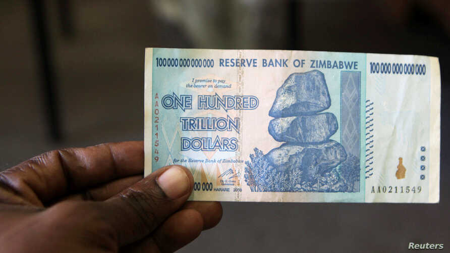 FILE - A man holds up for a picture a one hundred trillion Zimbabwean dollars note inside a shop in Harare, Zimbawe.