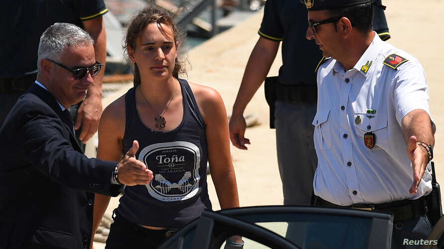 Carola Rackete, the 31-year-old Sea-Watch 3 captain, disembarks from a Finance police boat and is escorted to a car, in Porto Empedocle, Italy, July 1, 2019.