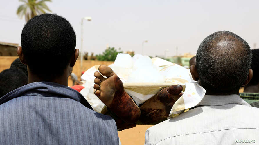 Locals and relatives of three Sudanese men riddled with bullets carry one of the bodies in the city of Omdurman across the River Nile from Khartoum, Sudan, July 1, 2019.