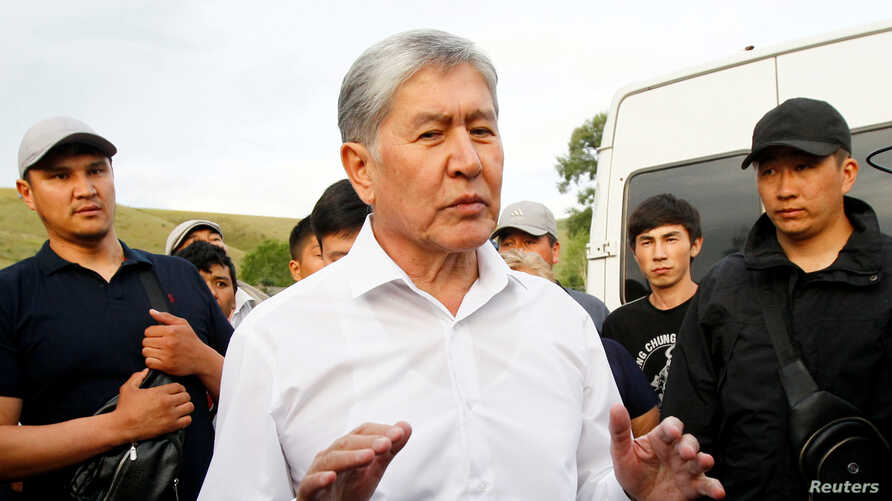 FILE - Kyrgyz former President Almazbek Atambayev, who was stripped of legal immunity after a parliamentary vote, and his supporters attend a meeting with journalists in the village of Koy-Tash near Bishkek, Kyrgyzstan June 27, 2019.