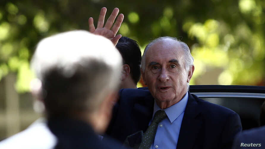 FILE - Former Argentine President Fernando de la Rua waves in front of a policeman as he arrives to a courtroom in Buenos Aires, Dec. 23, 2013.