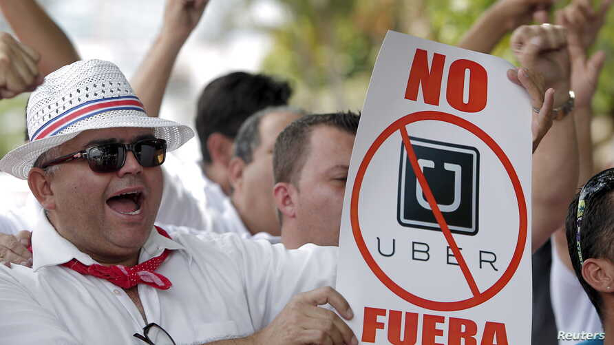 """FILE - A taxi driver holds a sign which reads """"No Uber, out"""" during a protest against car-sharing service Uber, outside the embassy of Colombia, in San Jose."""