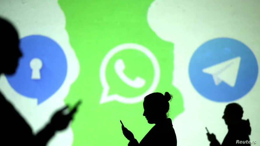 FILE - Silhouettes of mobile users are seen next to logos of social media apps Signal, Whatsapp and Telegram projected on a screen in this picture illustration.