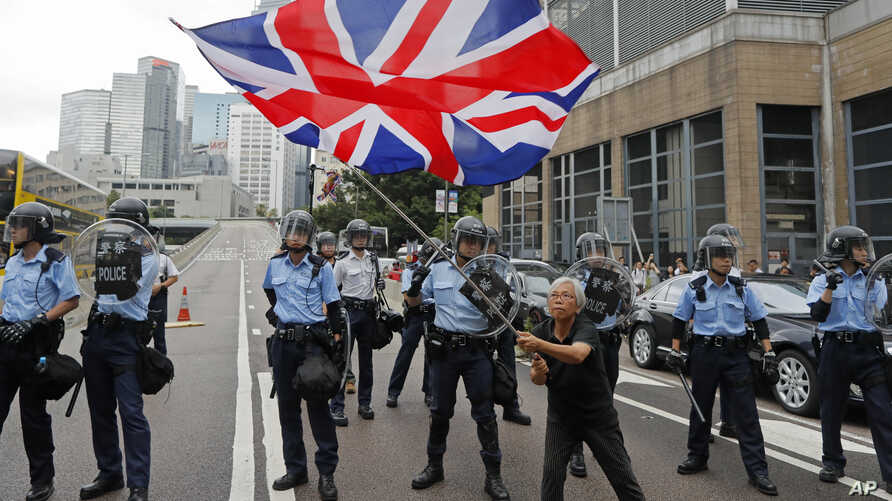 A woman waves a British flag as policemen in anti-riot gear stand guard against protesters on a closed-off road near the Legislative Council in Hong Kong, June 12, 2019.