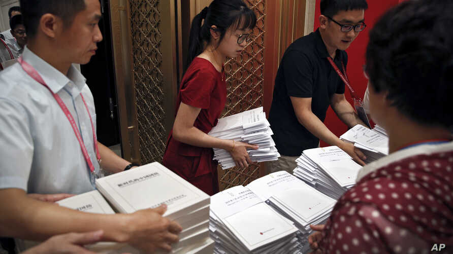 Workers prepare the China's national defense white paper to distribute to the reporters before a press conference at the State Council Information Office in Beijing,  July 24, 2019.
