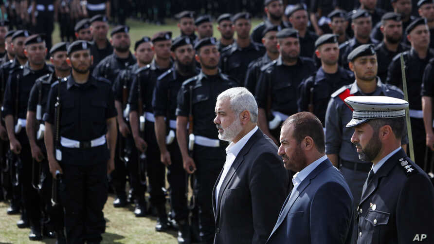 Fathi Hamad, Gaza's Hamas interior minister, second right, reviews honor guards during a graduation ceremony of Hamas security officers in the northern Gaza Strip, April 2, 2014.
