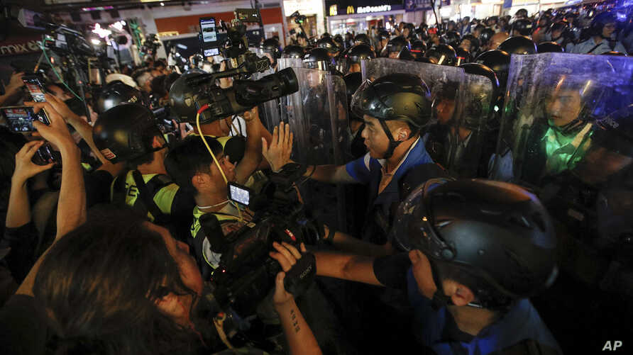 Journalists film policemen clearing a street in Hong Kong, July 7, 2019.